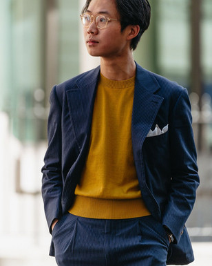 Buzz Tang wearing the mustard The Anthology knitted t-shirt with a navy seersucker suit