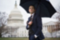 Picture of A Rake in Progress Author, David, wearing a Suitsupply suit and holding a Kent Wang umbrella in front of the U.S. Capitol