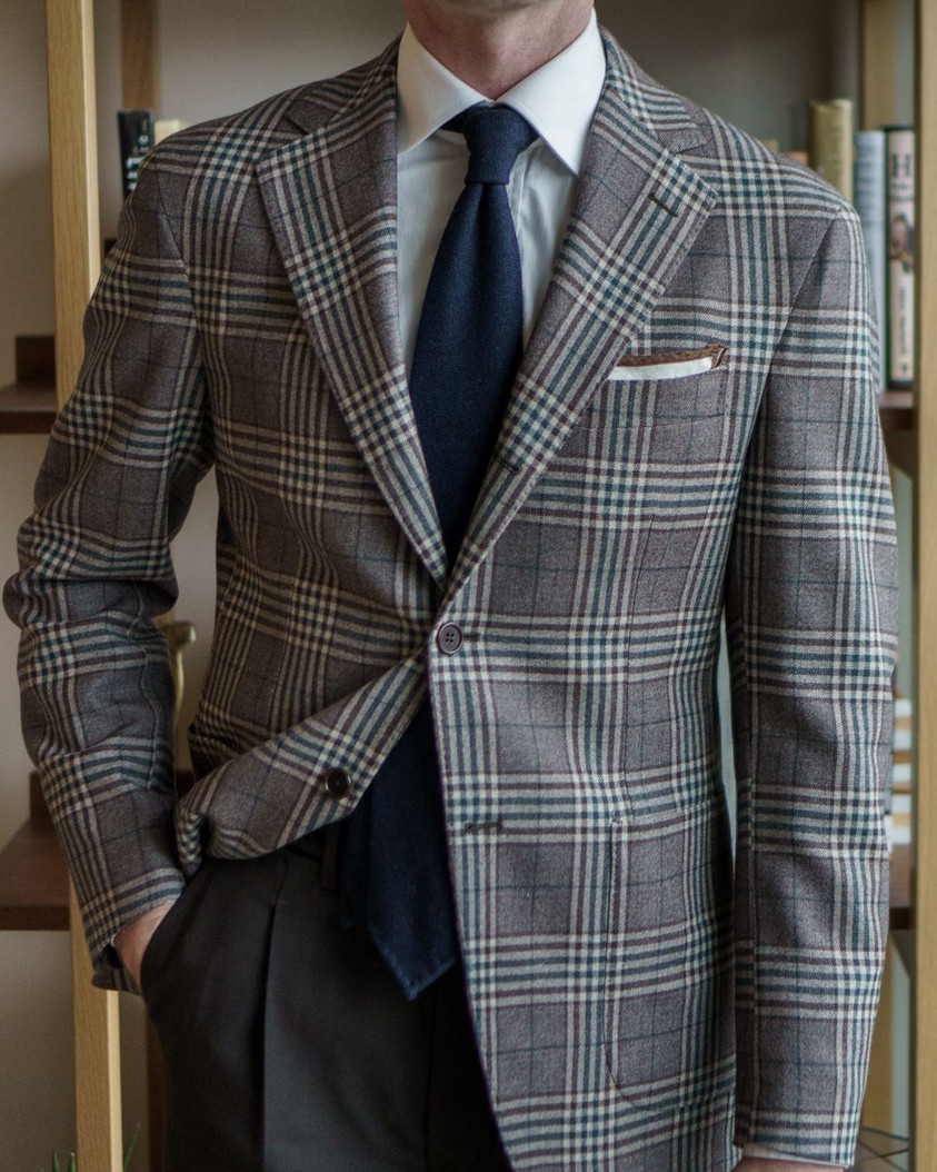 A Rake in Progress wears the Cavour beige check jacket, Anglo-Italian trousers, and navy wool tie from The Urban Tiesine tie