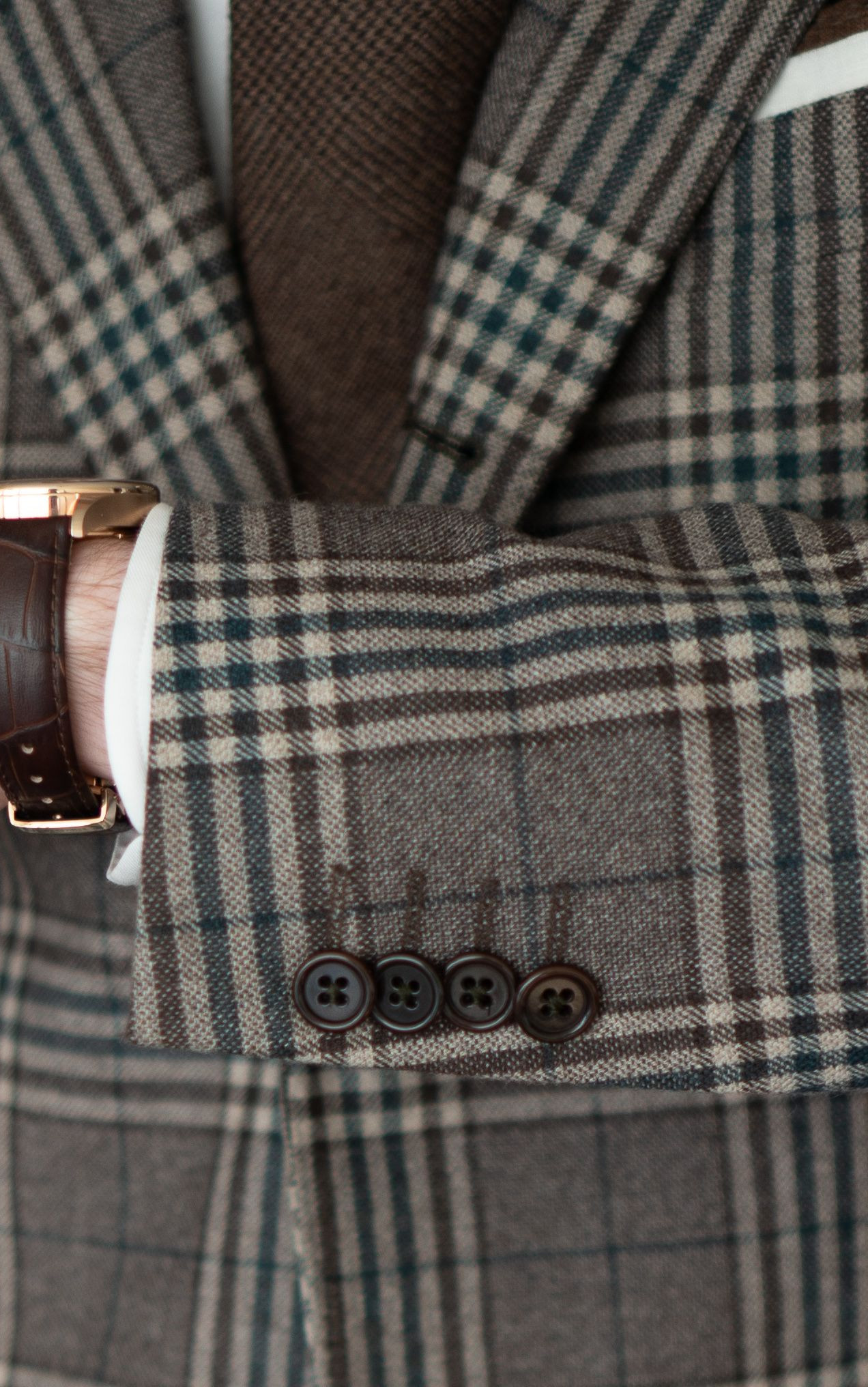 Close-up of the jacket cuff and buttons on the Cavour beige check jacket and the Tuseno First 38 watch