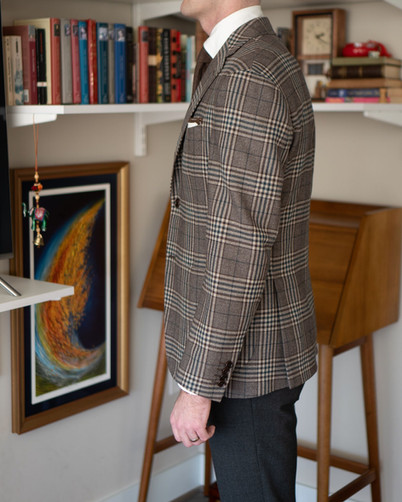 Left side view of A Rake in Progress wearing the Cavour beige check jacket and Anglo-Italian trousers