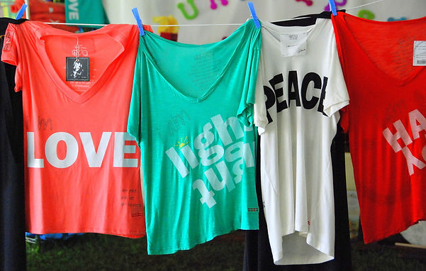 "A photo of 4 colorful shirts hanging on a line that say ""Love"", ""I am Light"", ""Peace"", and ""I am happy"""