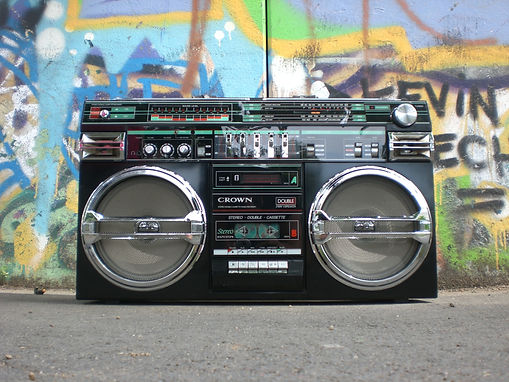 a close up photo of an old school boombox with colorful graffiti behind it