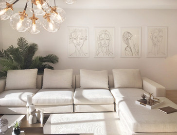 Four large artworks in a living room