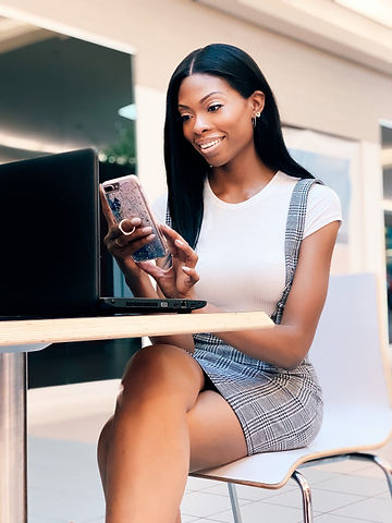 black woman on her cell phone and laptop
