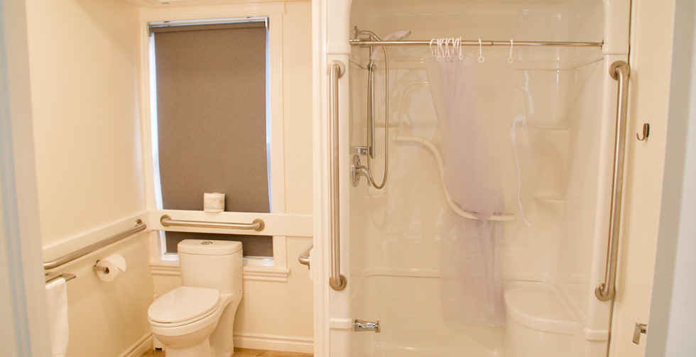 The bathroom has a large shower complete with bench and conforms to the bright and spacious design of the rest of the room.