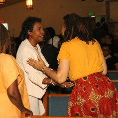 Congresswoman Clarke is greeted by Renee T. Gregory and Marilyn Reid