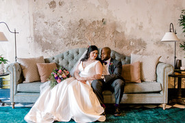 Couple poses on couch during first look photoshoot
