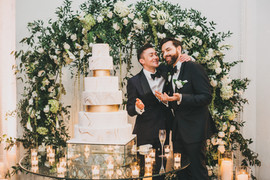 Two Grooms Cutting Wedding Cake