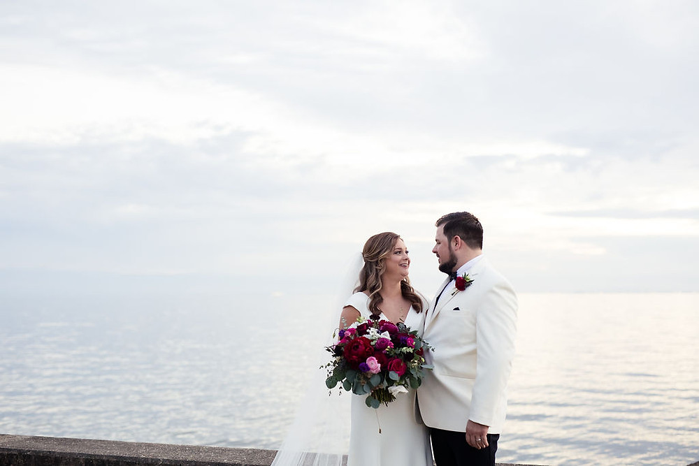 Bride and Groom at the riverfront - Bridal Bouquet with reds, pinks, and greenery