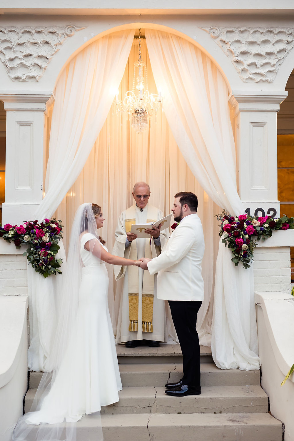 Bride and groom at their wedding ceremony with drapery, flowers, and a chandelier