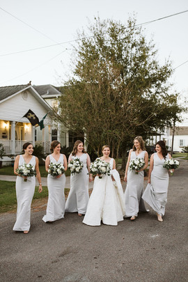Bridal party walks down road in uptown New Orleans