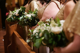 Bridesmaid in gold sequins stand in church ceremony