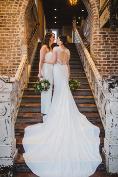 two brides with white and green bouquets