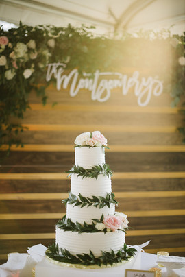 Flower and Greenery Dressed Cake with Elaborate Flower Garland Backdrop