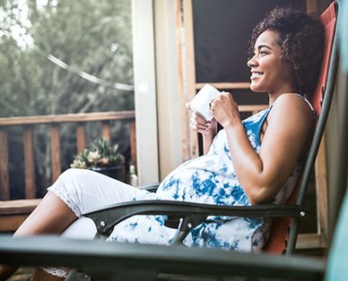 Smiling pregnant woman drinking from amug