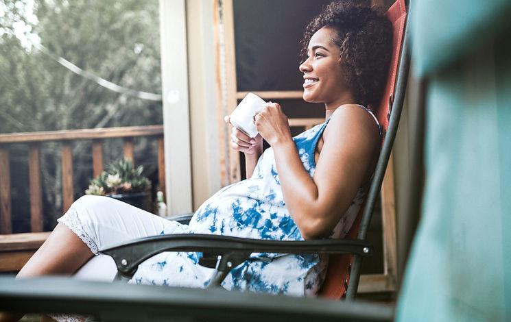 Pregnant mom enjoying drink on porch