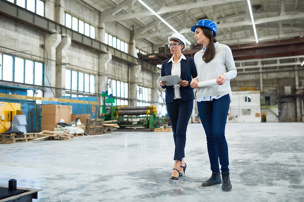 Two female general contractors walk through a staging area at a construction site