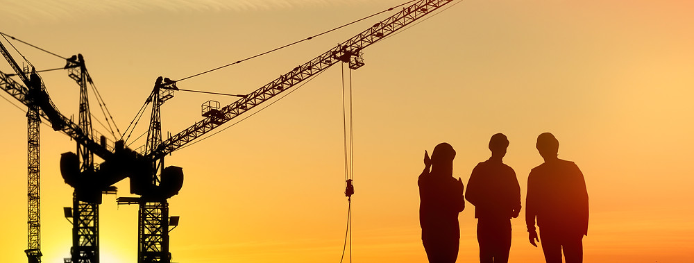 A woman shows two men progress on a construction site
