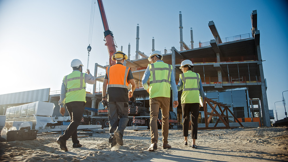 A group of men and a woman walk up to inspect a construction site in progress