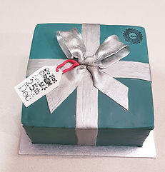 green Christmas present shaped fruit cake with silve ribbon and gift tag