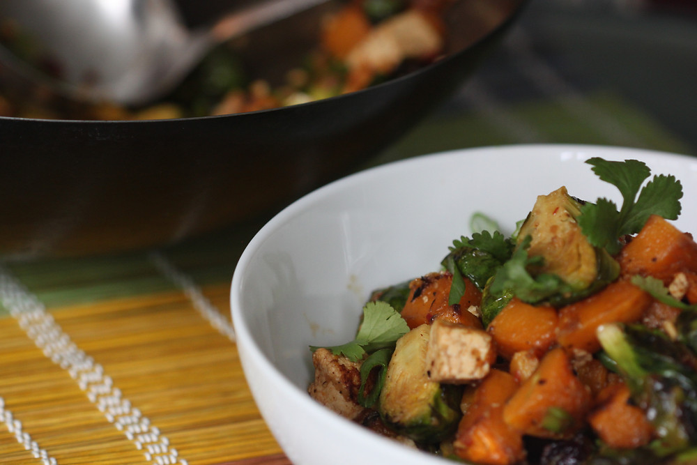 Brussel sprouts, butternut squash, tofu salad in a white serving bowl with the wok in the background