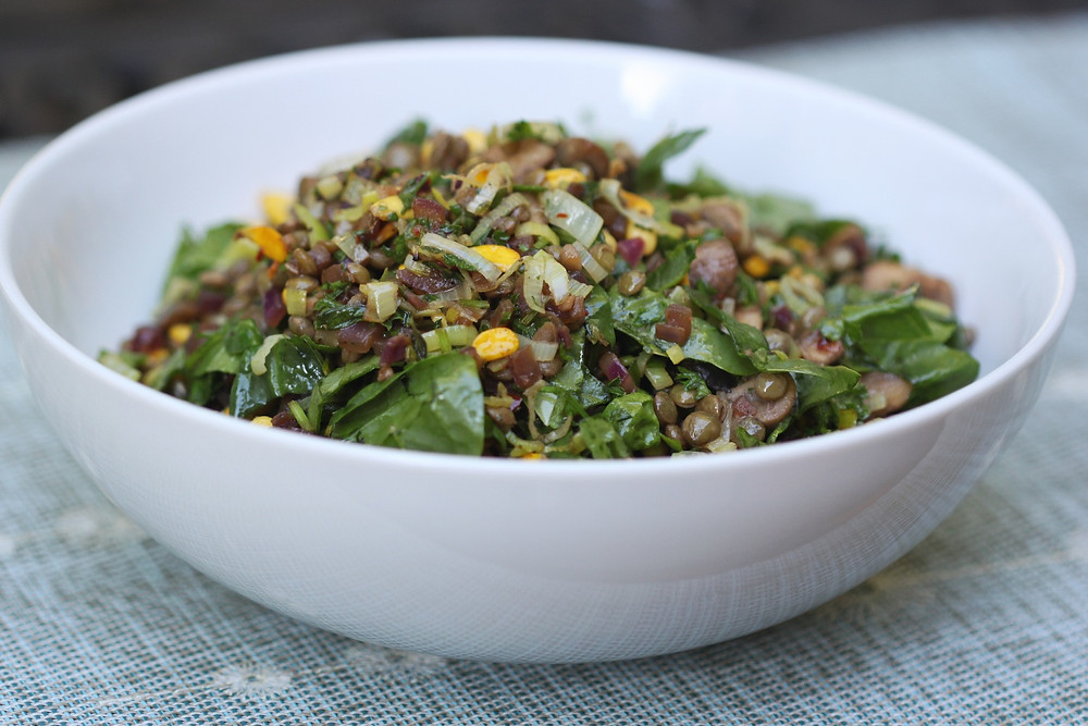 Healthy green lentil salad in a white bowl