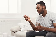 man-holding-glass-of-water-and-pill-taki