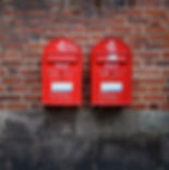 photo of two red post boxes mounted in brown concrete wall_edited.jpg