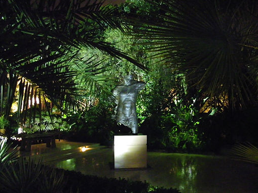 Statue lighting framed by silhouette of palm fronds for home in Palm Beach