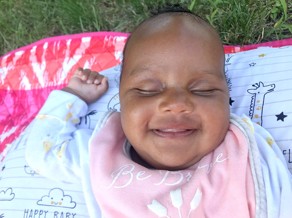 a 3 month old smiling on a bopper