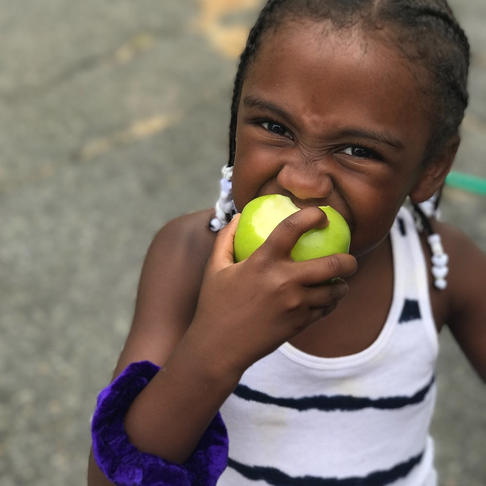 girl eating a green apple
