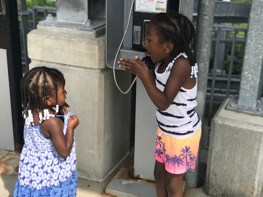 sisters playing on pay phone