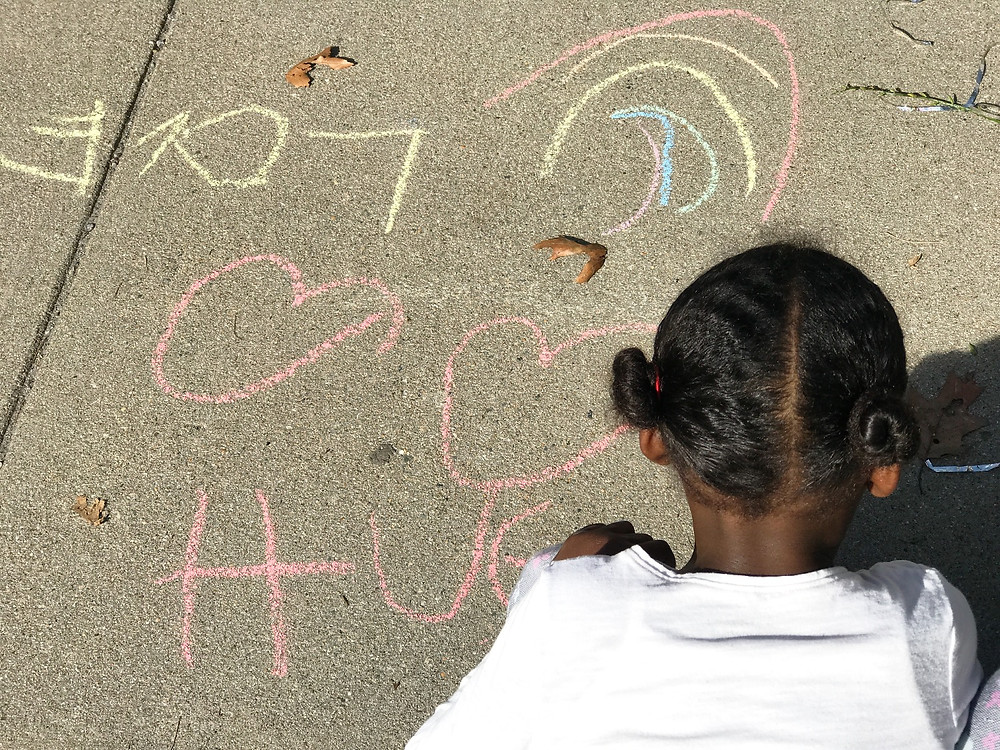homeschooler using sidewalk chalk