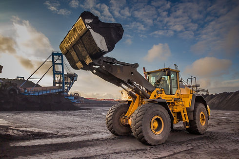 A bucket loader carries out loading of coal in an open port warehouse on a background of b