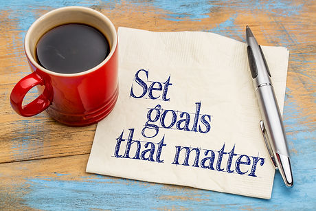 Set goals that matter  advice or reminder - handwriting on a napkin with cup of coffee against gray