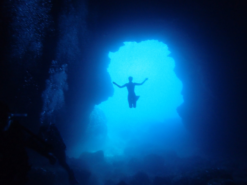 Freediver silhouette in entrance to cave Ibiza