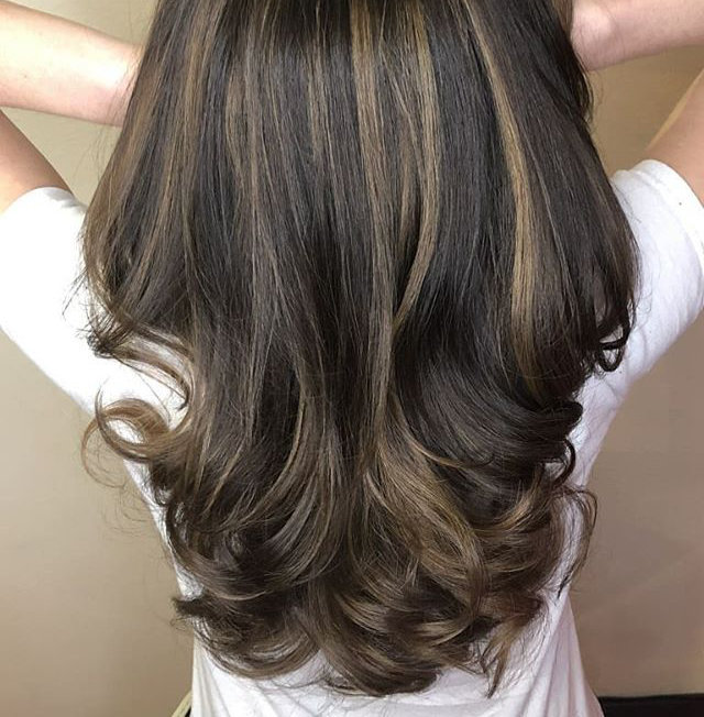 Juxtaposition of brick laying balayage of lightener and cool ash low lights on top on a rich neutral