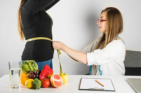 female-doctor-measuring-waist-woman-clin