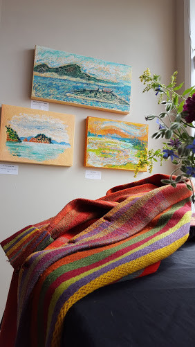"""""""Coat of many colours"""" with Violet's paintings in the background"""