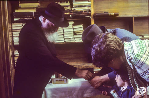 The Rebbe distributes coins to the children to be given to charity