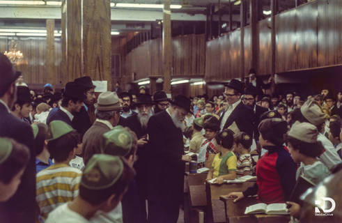 Entering a children's rally the Rebbe distributes coins to the children to be given to charity