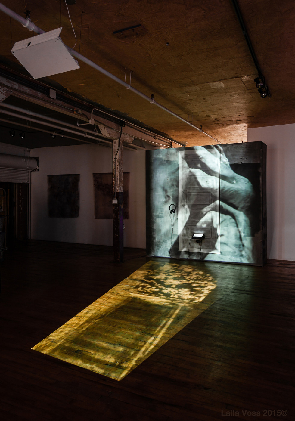 """Searching for that Sound Piece. 2010- 2015. Installation view with video projections of stairs and hands. Graphite rubbings on vellum and on the 8' x 8' wall, soundscape (T:00:11:34), DVD player, earphones, 2 projectors, two videos. Overall dimensions app: 8'20"""" x 8'4"""" x 23'.  Photo credit: Jerry Mann."""