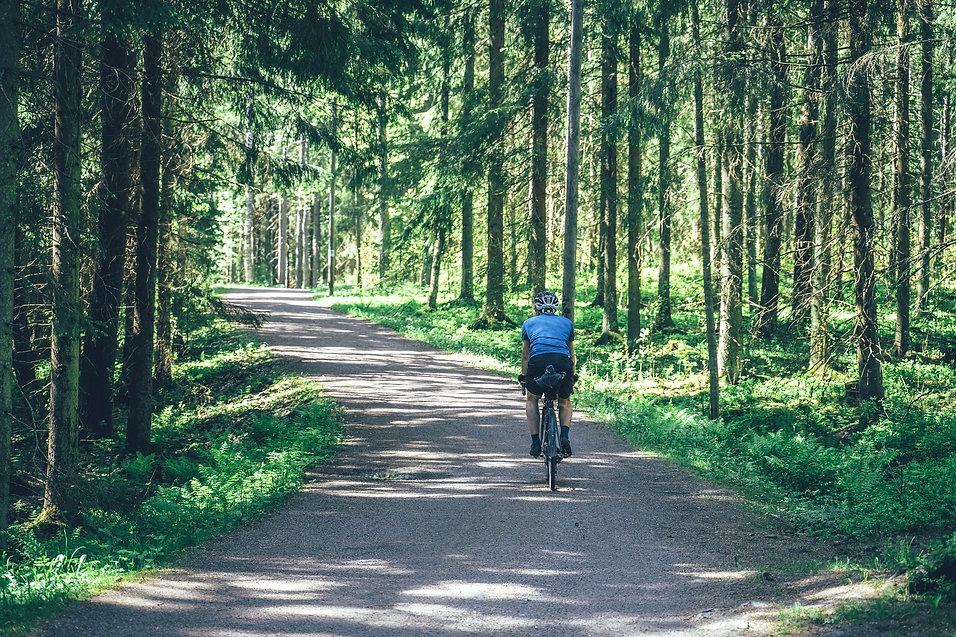 Gravel-pyöräilijä soratiellä metsässä