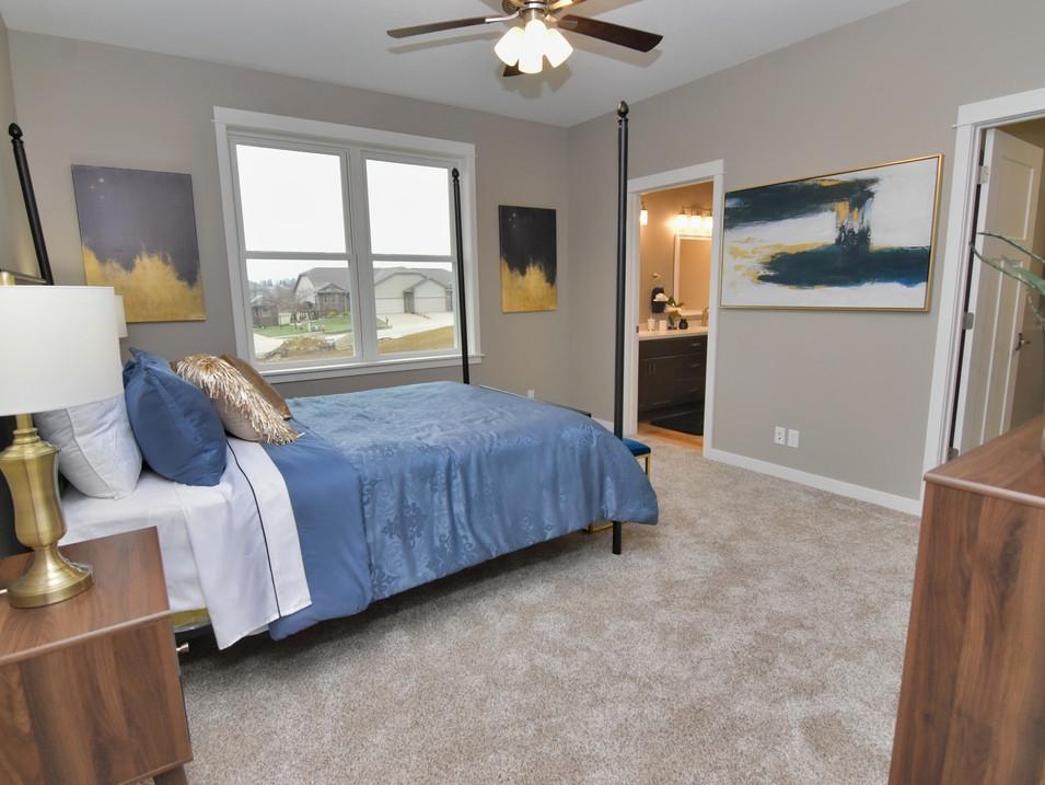 staged main bedroom in custom builders home