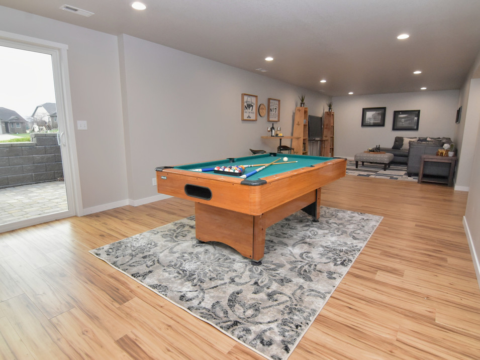 staged walk out basement game/media area in custom builders home