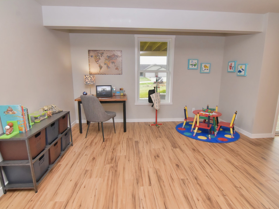 staged walk out basement homework/play room in custom builders home