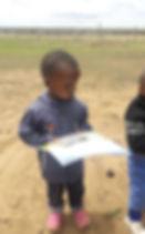 Child recieving crayon & pads
