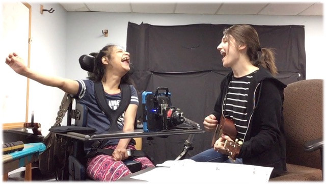 Music therapist singing and playing ukulele with a wheelchair bound client