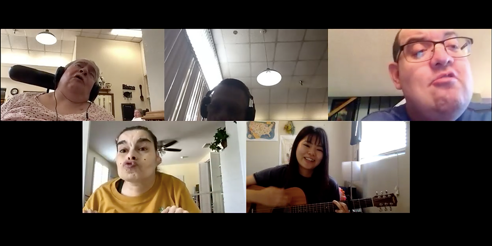 Zoom screenshot with Music Therapy Intern, Reon, in the bottom right panel. To row left to right: female singing in pink shirt in wheelchair, male with headphones, male wearing glasses and singing. Bottom row left to right: female in yellow shirt singing, Reon smiling and singing while playing guitar.